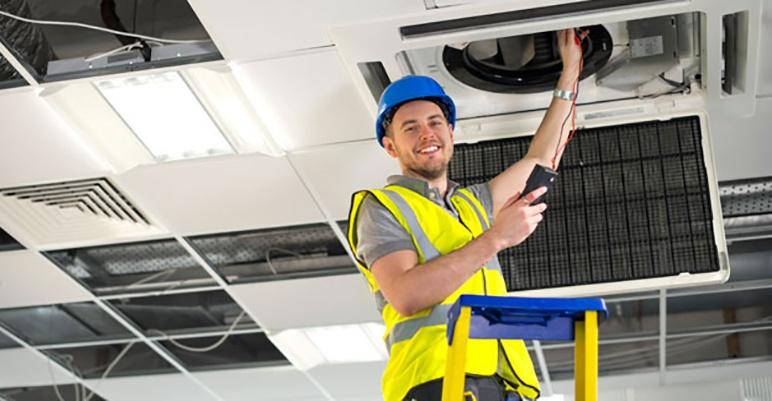 HVAC technician repairing HVAC unit